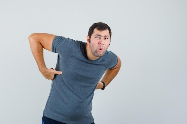 Młody mężczyzna w szarym t-shircie cierpi na bóle pleców i wygląda na zmęczonego