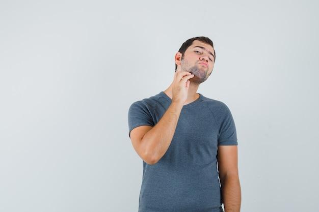 Młody mężczyzna w szarym t-shircie dotykając brody i wyglądając elegancko