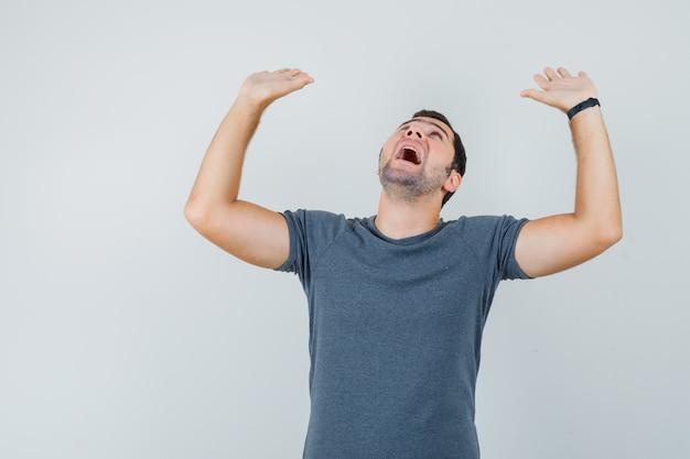 Młody mężczyzna w szarym t-shircie prewencyjnie unoszący dłonie i wyglądający na przestraszonego