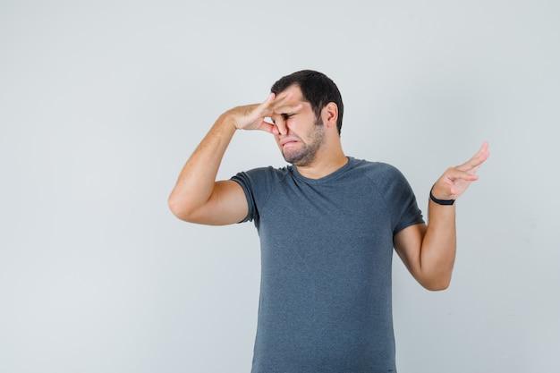 Młody mężczyzna w szarym t-shircie szczypie nos z powodu nieprzyjemnego zapachu i wygląda na zniesmaczonego