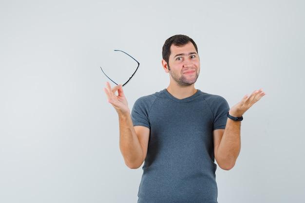Młody mężczyzna w szarym t-shircie trzymając okulary, rozkładając dłoń i wyglądający optymistycznie