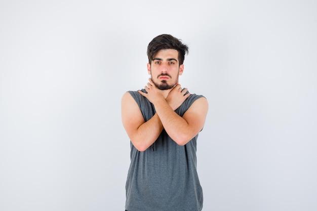 Młody mężczyzna w szarym t-shircie trzymający skrzyżowane ręce i wyglądający poważnie