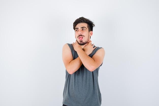 Młody mężczyzna w szarym t-shircie trzymający skrzyżowane ręce, odwracający wzrok i patrzący poważnie