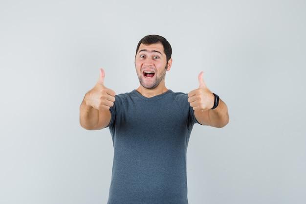 Młody mężczyzna w szarym t-shircie z podwójnymi kciukami do góry i wyglądającym wesoło