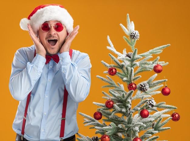 Młody mężczyzna w szelkach muszka w czapce mikołaja i czerwonych okularach stoi obok choinki zdumiony i zaskoczony pomarańczową ścianą