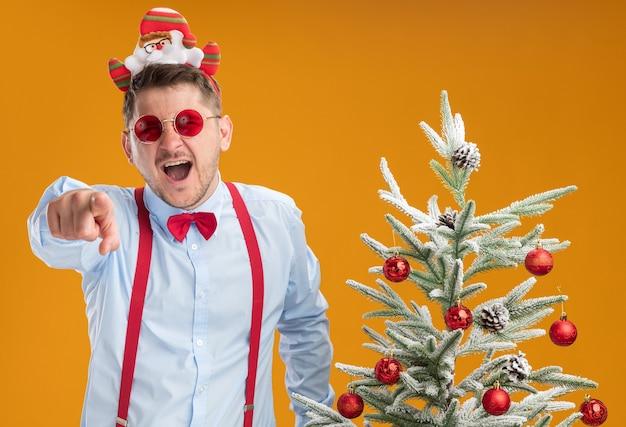 Młody mężczyzna w szelkach muszka w obręczy z mikołajem i czerwonymi okularami stojący obok choinki śmiejąc się, wskazując palcem wskazującym na ciebie nad pomarańczową ścianą