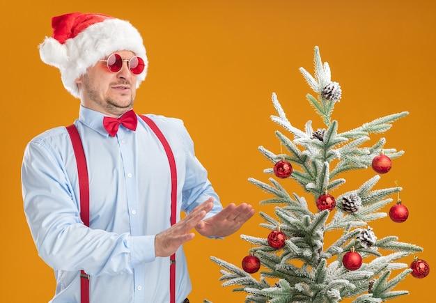 Młody mężczyzna w szelkach z muszką w czapce mikołaja i czerwonych okularach stoi obok choinki patrząc na nią z obrzydzonym wyrazem twarzy, trzymając ręce wyciągnięte nad pomarańczową ścianą