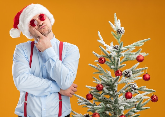 Młody mężczyzna w szelkach z muszką w czapce mikołaja i czerwonych okularach stoi obok choinki, patrząc z ręką na brodzie i myśląc o pomarańczowej ścianie