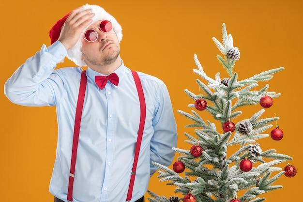 Młody mężczyzna w szelkach z muszką w czapce mikołaja i czerwonych okularach stoi obok choinki, patrząc zdziwiony ręką na głowie nad pomarańczową ścianą
