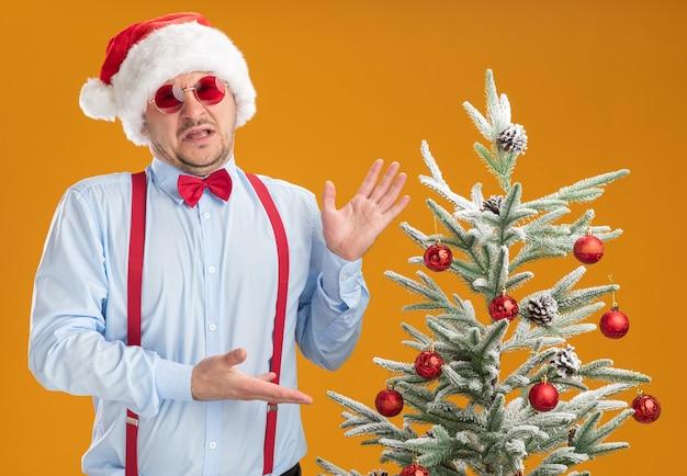 Młody mężczyzna w szelkach z muszką w czapce mikołaja i czerwonych okularach stoi obok choinki, prezentując ją z rękami zdenerwowanymi i niezadowolonymi na pomarańczowej ścianie