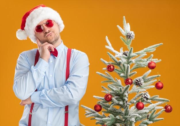 Młody mężczyzna w szelkach z muszką w czapce mikołaja i czerwonych okularach stoi obok choinki z zamyślonym wyrazem twarzy, myśląc o pomarańczowej ścianie