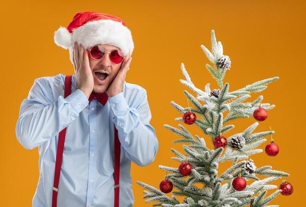 Młody mężczyzna w szelkach z muszką w czapce mikołaja i czerwonych okularach zdumiony i zdziwiony stojąc obok choinki nad pomarańczową ścianą