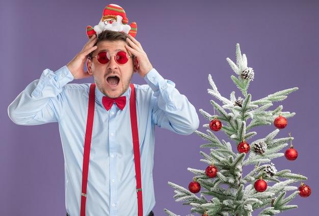 Młody mężczyzna w szelkach z muszką w obręczy z mikołajem i czerwonymi okularami stoi obok choinki zdumiony i zaskoczony z rękami na głowie nad fioletową ścianą
