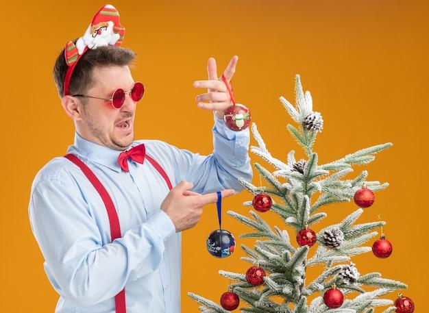 Młody mężczyzna w szelkach z muszką w obręczy z mikołajem i czerwonymi okularami stojący obok choinki wyglądający na zdezorientowanego, próbujący dokonać wyboru, trzymając zabawki dla drzewa na pomarańczowym tle