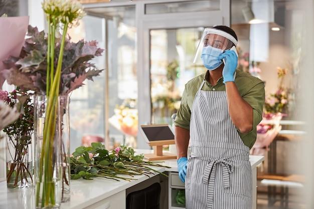 Młody mężczyzna w szkle ochronnym i masce dzwoni podczas robienia bukietów w kwiaciarni