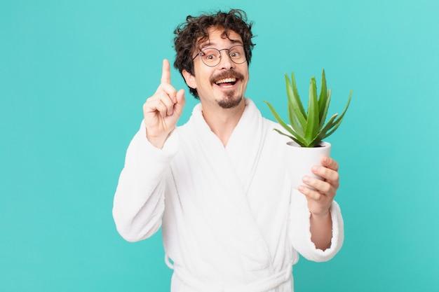Młody mężczyzna w szlafroku czuje się jak szczęśliwy i podekscytowany geniusz po zrealizowaniu pomysłu