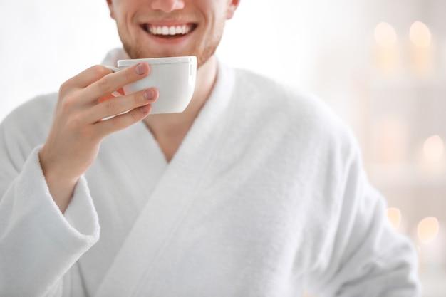 Młody mężczyzna w szlafroku pije kawę w domu