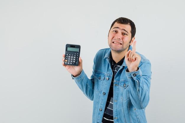 Młody mężczyzna w t-shircie, gestykulacji marynarki, czekaj chwilę, trzymający kalkulator i wyglądający na bezradnego