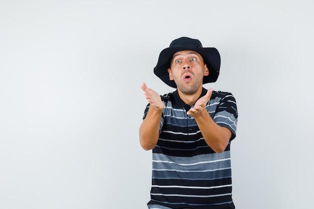 Młody mężczyzna w t-shircie, kapeluszu, próbuje coś wyjaśnić i wygląda na podekscytowanego, widok z przodu.