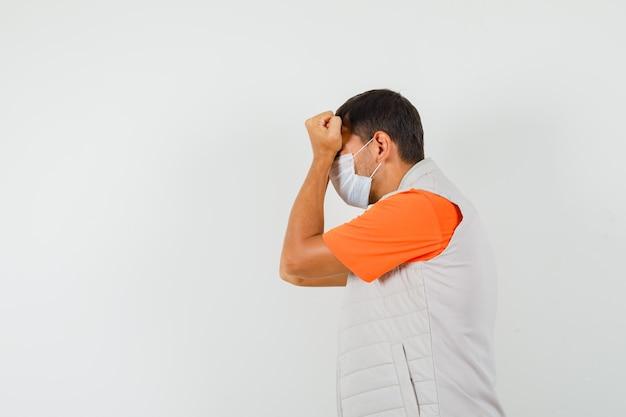 Młody mężczyzna w t-shircie, kurtce, masce, przyciskający pięści do czoła i wyglądający na spiętego.