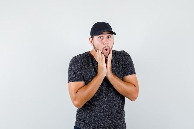 Młody mężczyzna w t-shirt i czapce, dżinsy, trzymając się za ręce w pobliżu otwartych ust i wyglądając na zszokowanego