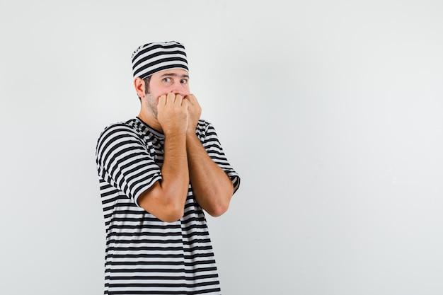 Młody mężczyzna w t-shirt, kapelusz gryzący pięści emocjonalnie i wyglądający na przestraszonego, widok z przodu.
