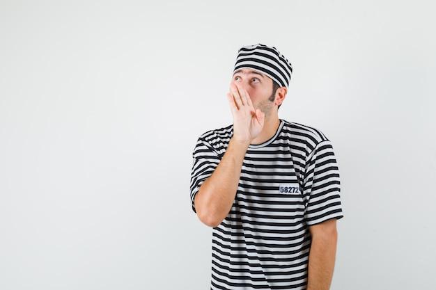 Młody mężczyzna w t-shirt, kapelusz mówi sekret za ręką, widok z przodu.