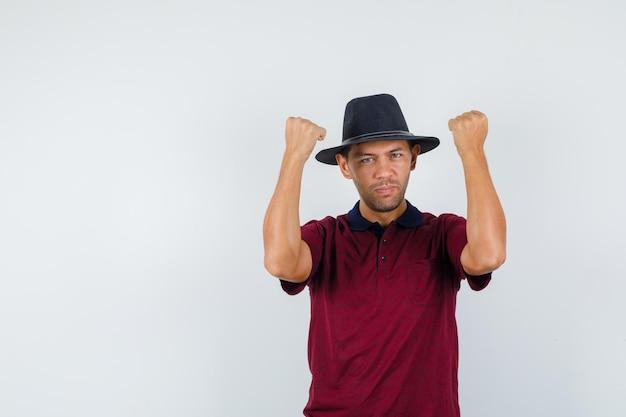 Młody mężczyzna w t-shirt, kapelusz podnoszący zaciśnięte pięści i wyglądający na silnego, widok z przodu.