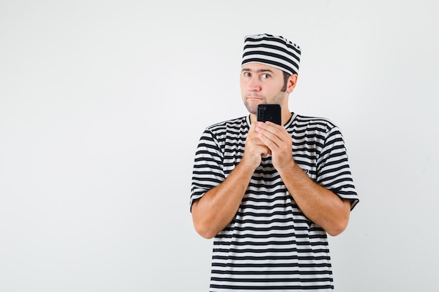 Młody mężczyzna w t-shirt, kapelusz, trzymając telefon komórkowy i patrząc zamyślony, widok z przodu.