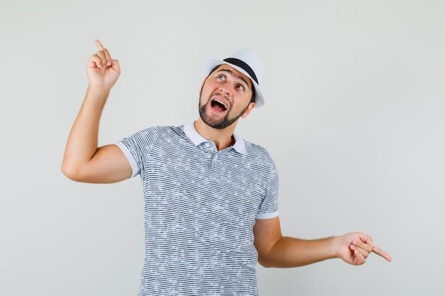 Młody mężczyzna w t-shirt, kapelusz wskazując palce w górę iw dół i patrząc wesoły, widok z przodu.