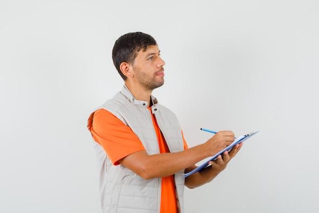 Młody mężczyzna w t-shirt, kurtka, robienie notatek w schowku, patrząc na bok, widok z przodu.