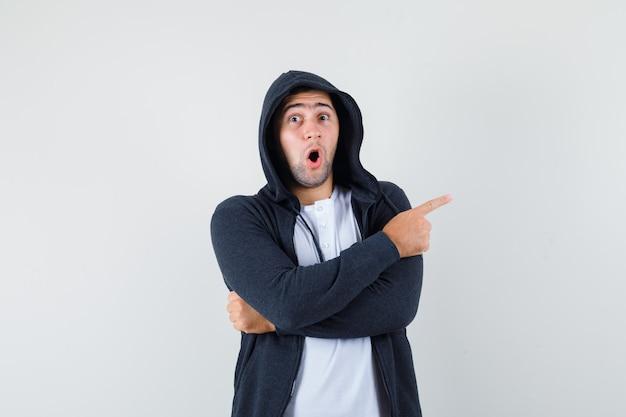 Młody mężczyzna w t-shirt, kurtka skierowana w prawą stronę i wyglądający na zaskoczonego, widok z przodu.