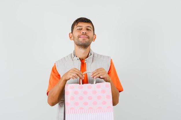 Młody mężczyzna w t-shirt, kurtka, trzymając torby na zakupy i patrząc jowialnie, widok z przodu.