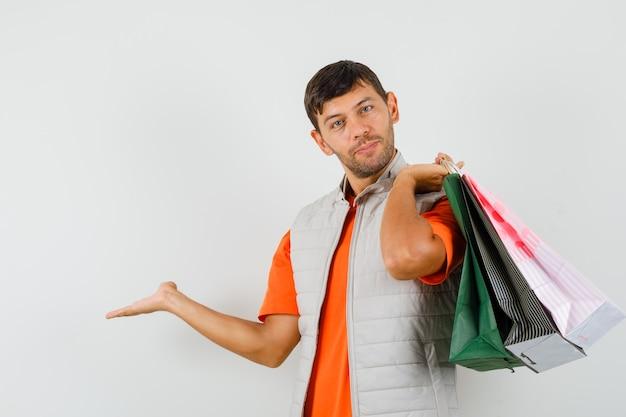 Młody mężczyzna w t-shirt, kurtka, trzymając torby na zakupy i witający i wyglądający genialnie, widok z przodu.