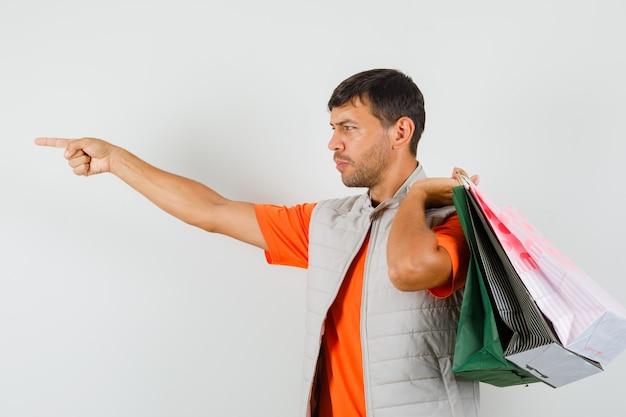 Młody mężczyzna w t-shirt, kurtka, trzymając torby na zakupy, wskazując i patrząc skupiony, widok z przodu.