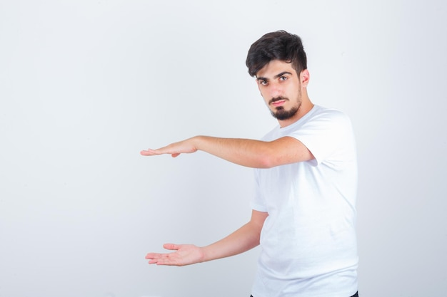 Młody mężczyzna w t-shirt pokazujący znak rozmiaru i wyglądający pewnie, widok z przodu.