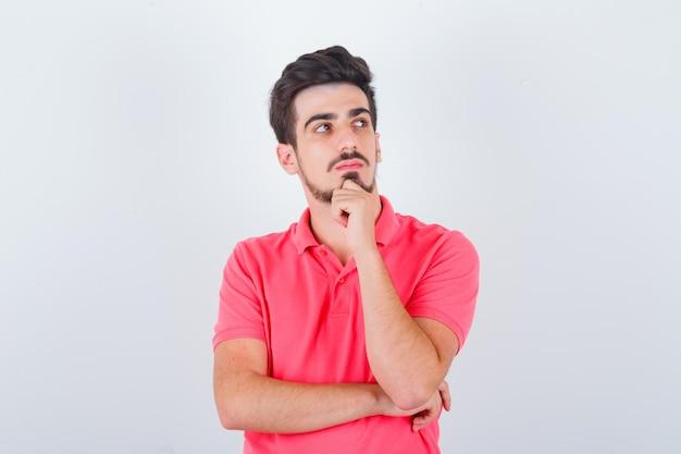 Młody mężczyzna w t-shirt stojący w myślącej pozie i patrząc rozsądnie, przedni widok.