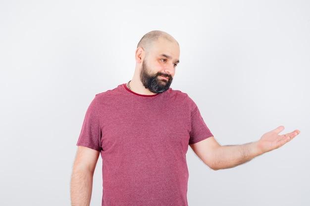 Młody mężczyzna w t-shirt udaje, że coś pokazuje i wygląda radośnie, widok z przodu.