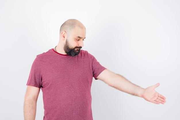 Młody Mężczyzna W T-shirt Udaje, że Coś Pokazuje I Wygląda Wesoło, Widok Z Przodu. Darmowe Zdjęcia