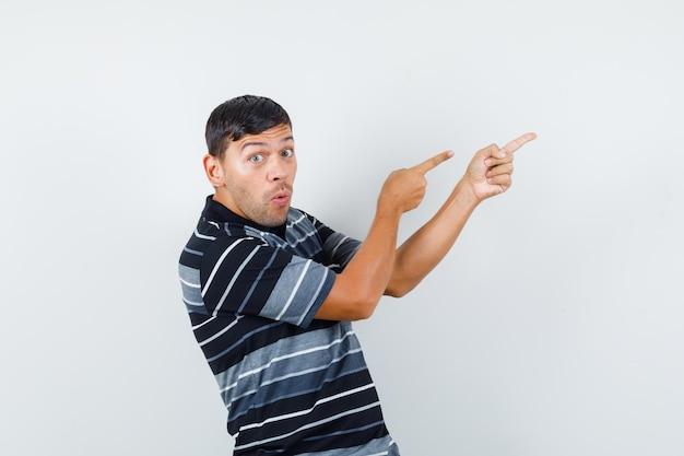 Młody mężczyzna w t-shirt, wskazując daleko i patrząc przestraszony, widok z przodu.