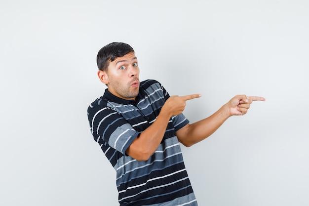 Młody mężczyzna w t-shirt wskazuje bok i wygląda przestraszony, przedni widok.