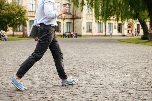 Młody mężczyzna w wizytowym, idąc ulicą miasta trzymając kawę na wynos i srebrny laptop