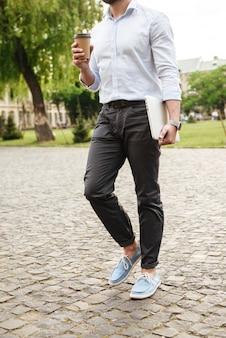 Młody mężczyzna w wizytowym, spacerując po zielonym parku z kawą na wynos i srebrnym laptopem
