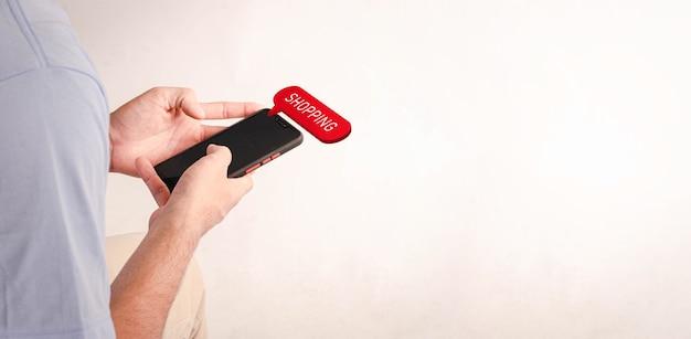 Młody mężczyzna w wolnym czasie szuka sklepu na zakupy na swoim telefonie komórkowym.