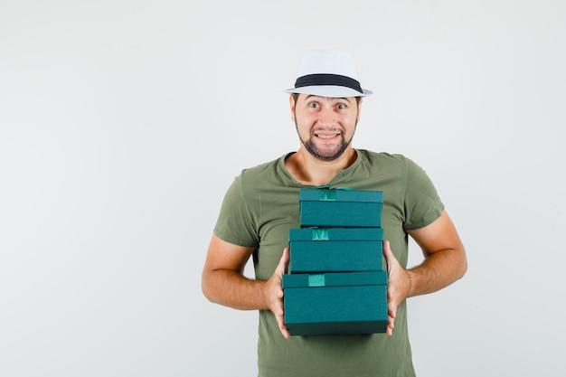 Młody mężczyzna w zielonej koszulce i kapeluszu, trzymając obecne pudełka i patrząc optymistycznie