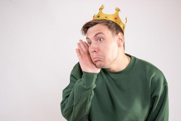 Młody mężczyzna w zielonej koszulce z koroną na głowie na białym tle