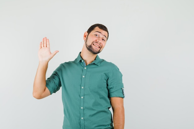 Młody mężczyzna w zielonej koszuli machając ręką na powitanie i patrząc radosny, widok z przodu.