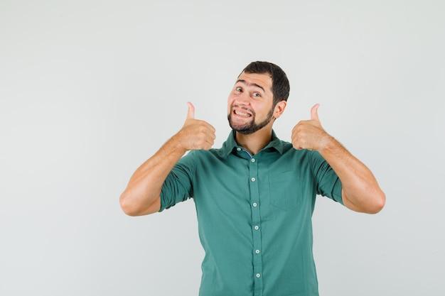 Młody mężczyzna w zielonej koszuli pokazując kciuk do góry i patrząc szczęśliwy, widok z przodu.