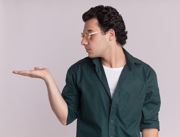 Młody mężczyzna w zielonej koszuli w okularach, patrząc na bok, prezentując z ramieniem dłoni kopia przestrzeń stojącą nad białą ścianą