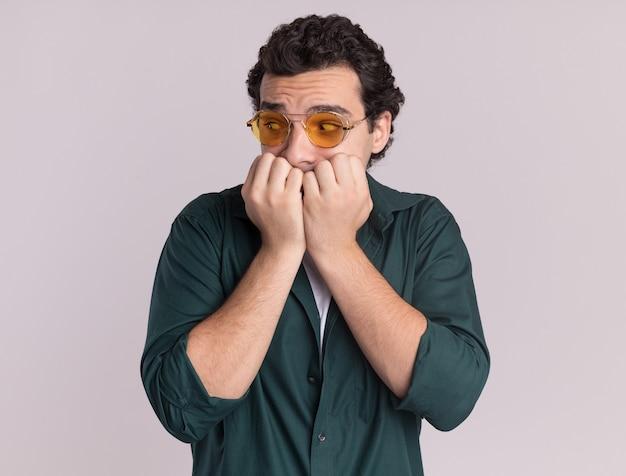 Młody mężczyzna w zielonej koszuli w okularach patrząc na bok zestresowany i nerwowy gryzienie paznokci stojących na białej ścianie